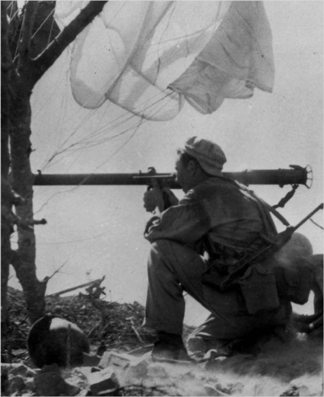 Американский десантник, вооруженный  карабином M1A1 со складным прикладом и ручным противотанковым гранатометом Базука, ведет огонь по ДОТу на острове Коррехидор в ходе битвы за Батаан.