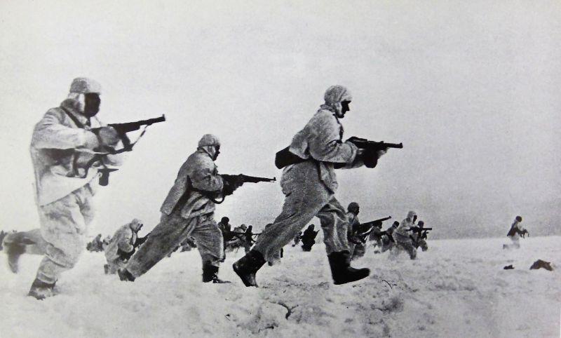 Красноармейцы в зимних маскхалатах бегут по полю. Согласно источнику, снято во время боев на можайском направлении.