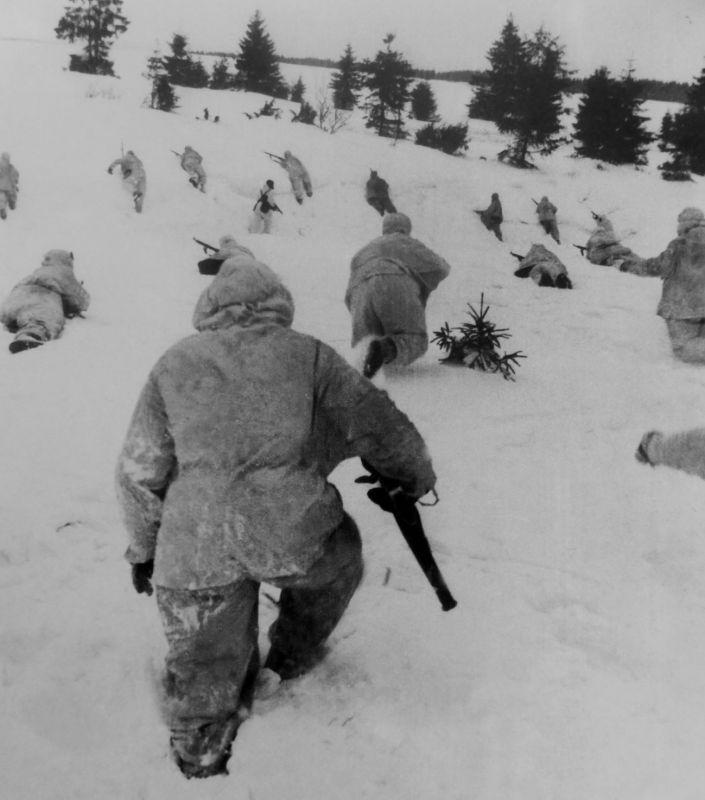 Красноармейцы в зимних маскхалатах передвигаются к склону холма. Контрнаступление под Москвой.
