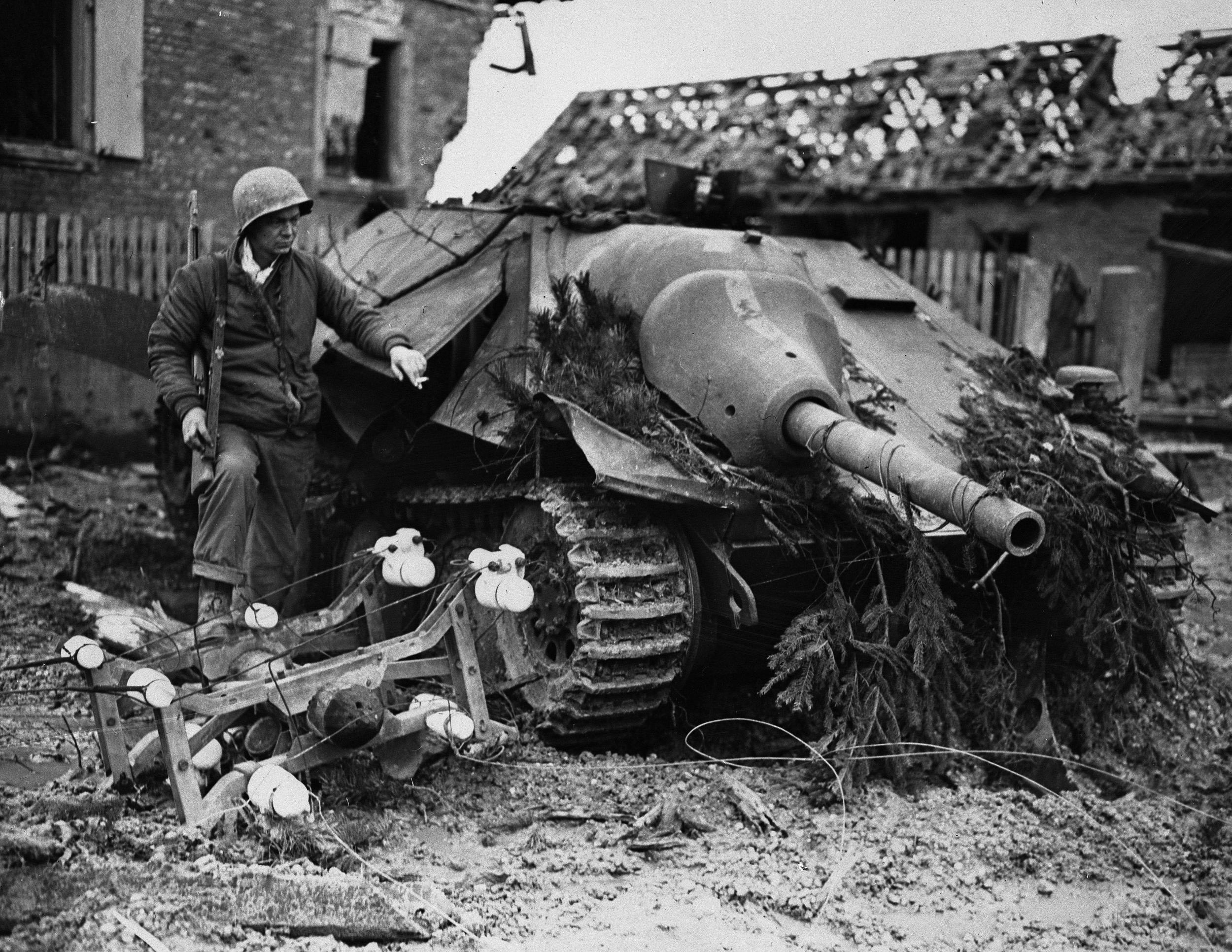 Рядовой Кеннет Уокер осматривает немецкую САУ «Хетцер», подбитую в коммуне  Оберхоффен — военное фото