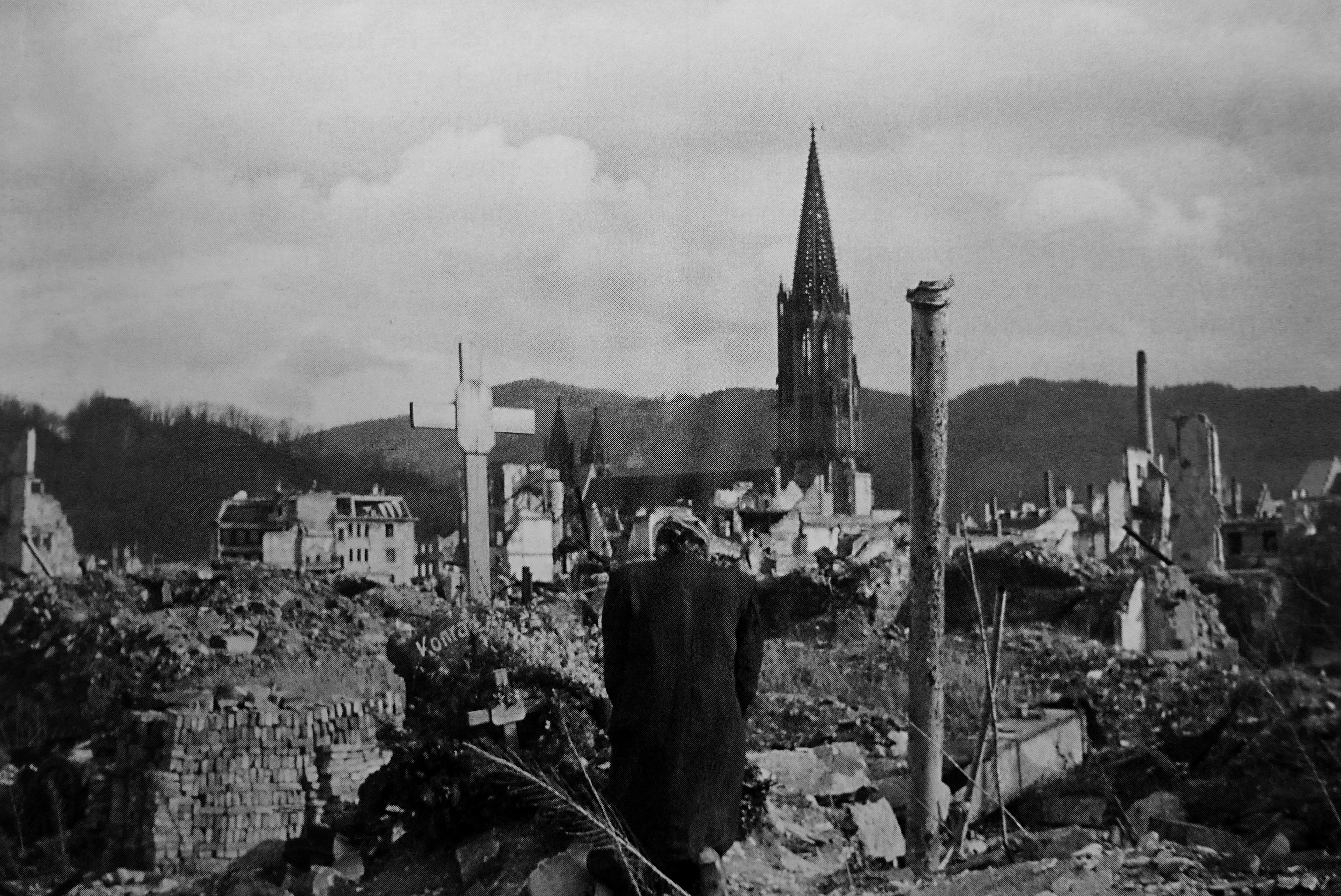 Фото: Жительница Фрайбурга перед крестами на месте разрушенного дома в центре города
